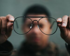 man holding eyeglasses